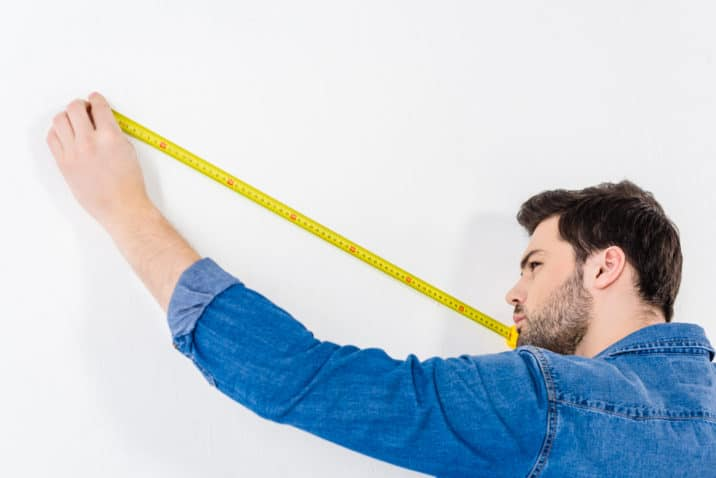 Man holding a measuring tape in a white background
