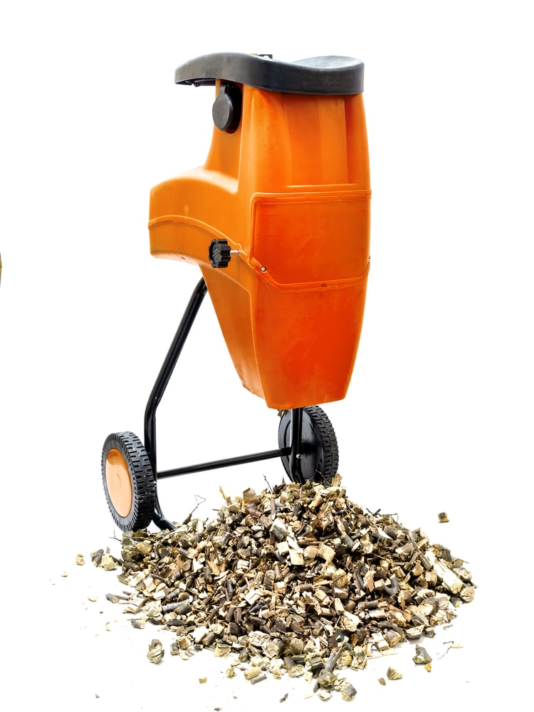 Electric wood shredder with wood chips used for garden mulching shot on white