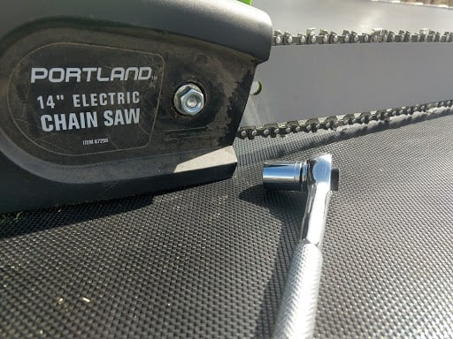 Chainsaw and a socket wrench laid down on a flat surface