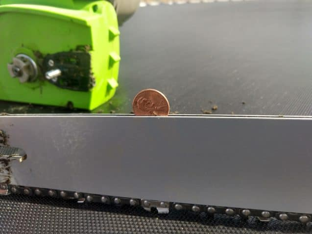 A coin placed in between chainsaw metal plates with chainsaw chains removed