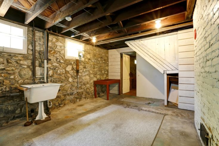 Basement empty room interior with stone wall trim and brick wall with fireplace. Room with old sink