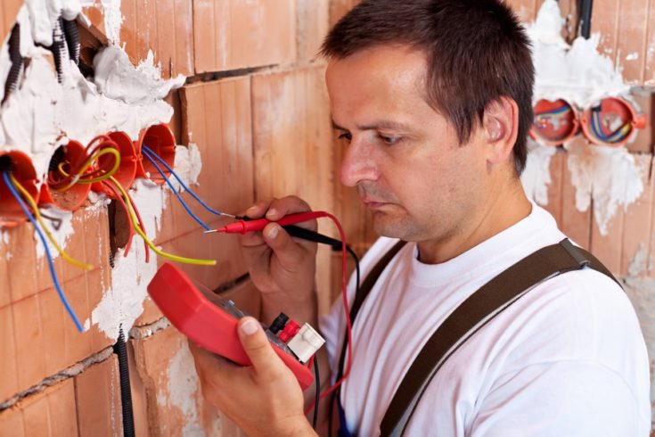 Electrician working - measuring the wiring in a new house