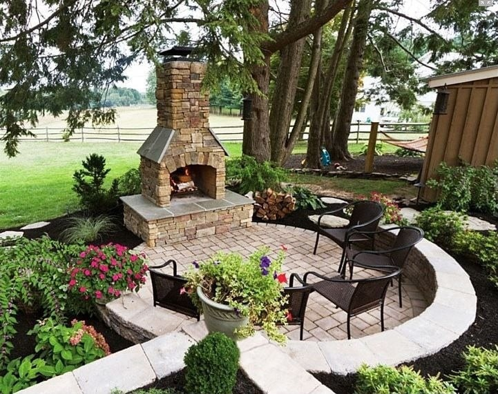 Outdoor fireplaces with five black chairs on the garden