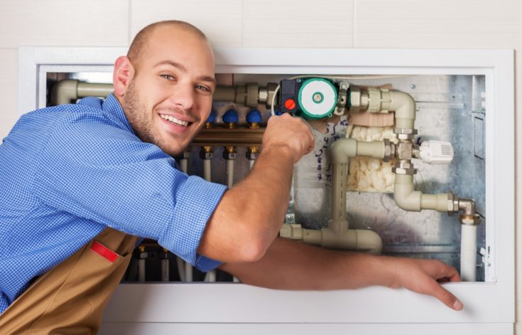 Professional plumber fixing pipes