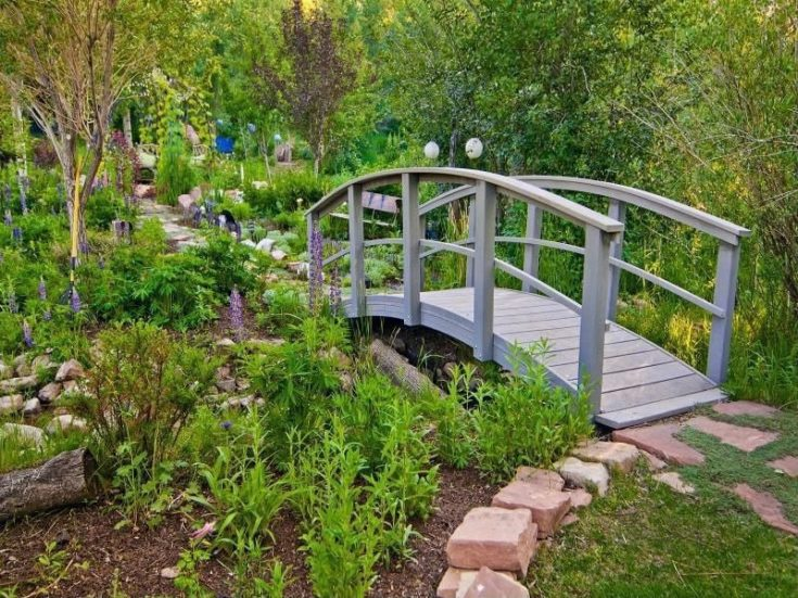 a garden with grey arc wooden bridge