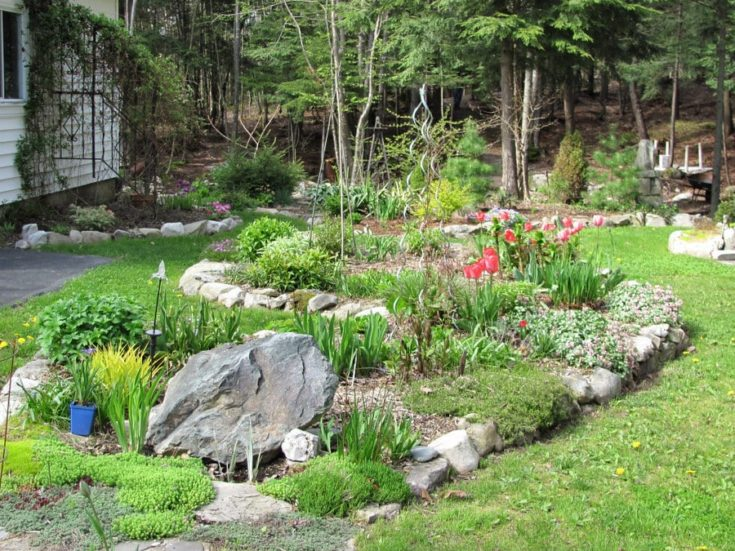 a garden with with well-placed rocks, perennial plantings, and even fencing options