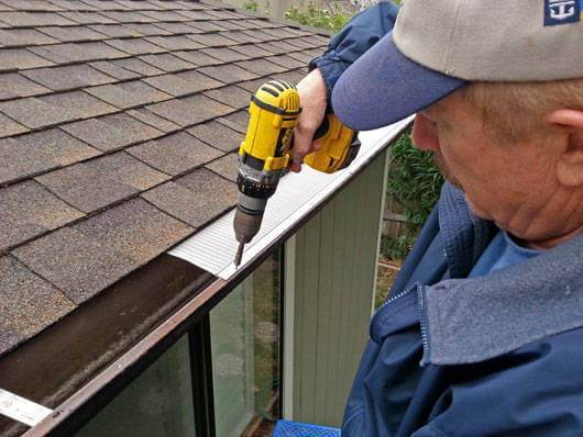 a person installing easyon gutter guard on the roof