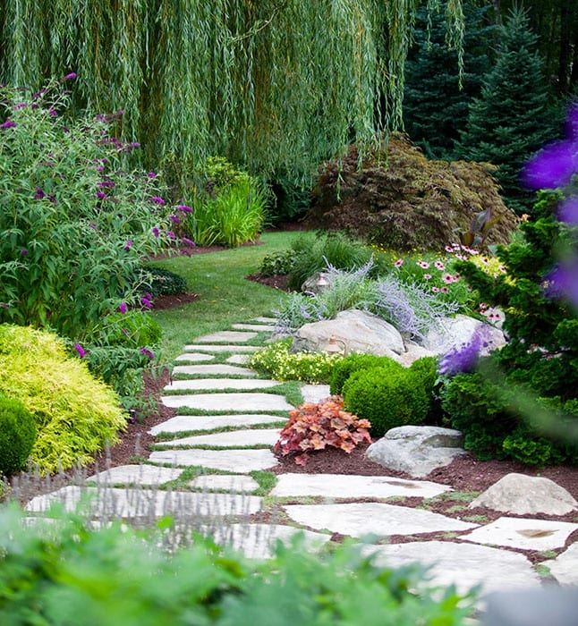 lovely flagstone walkway ends at the edge of a garden