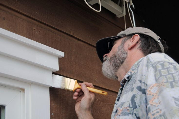A senior man painting the doorway with white paint