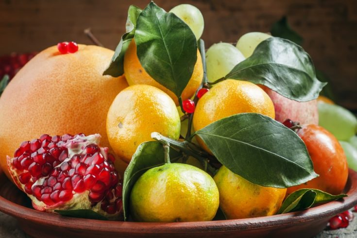 Clay dish with winter fruits: grapefruit, tangerines, persimmons, pomegranates with leaves on the old wooden table, still life, selective focus