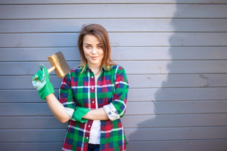 Young working woman with paint brush, freshly painted wooden exterior wall behind her, handy woman concept