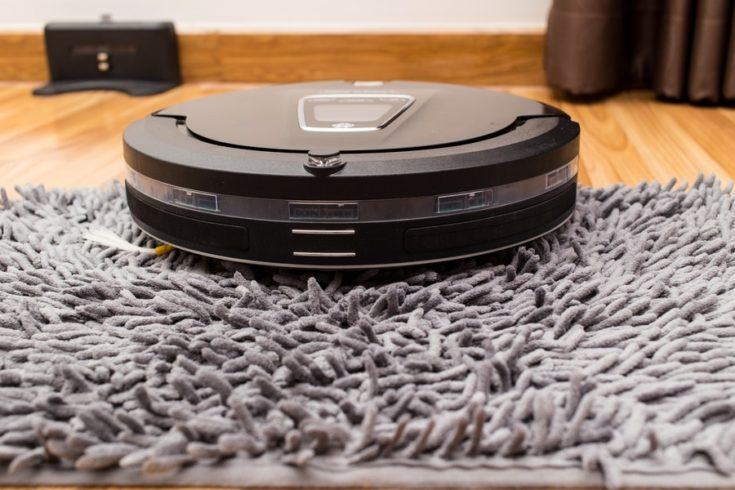Robotic vacuum cleaner on wood parquet floor, Smart vacuum, new automate technology housework - Cleaning on carpet.