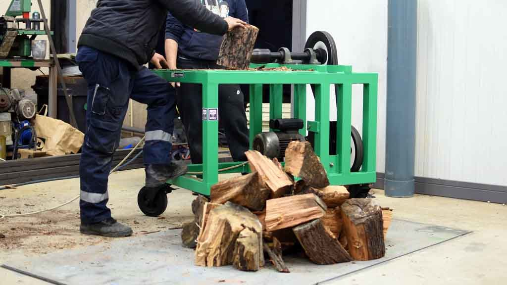 a man cutting a log using screw log splitter machine