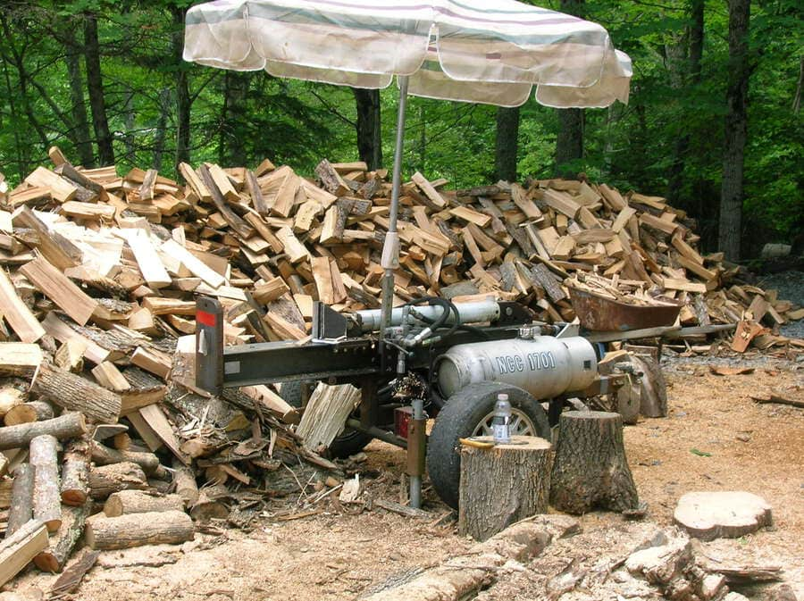 a custom small log splitter with cut logs around it on the backyard