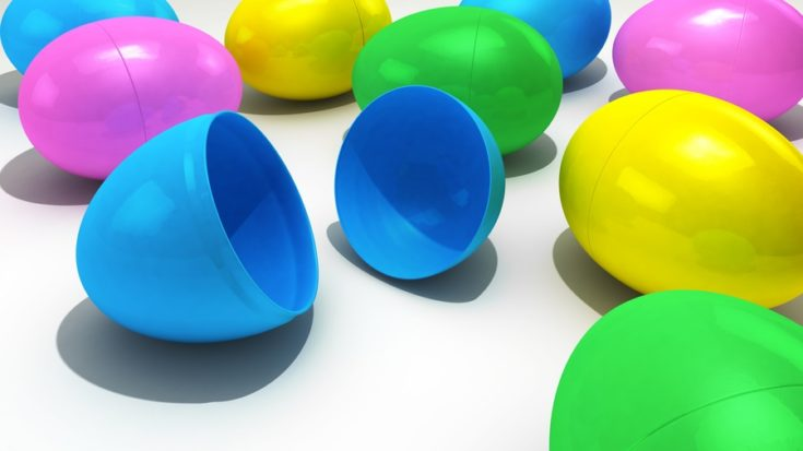A collection of pastel colored plasic Easter eggs over a bright white background
