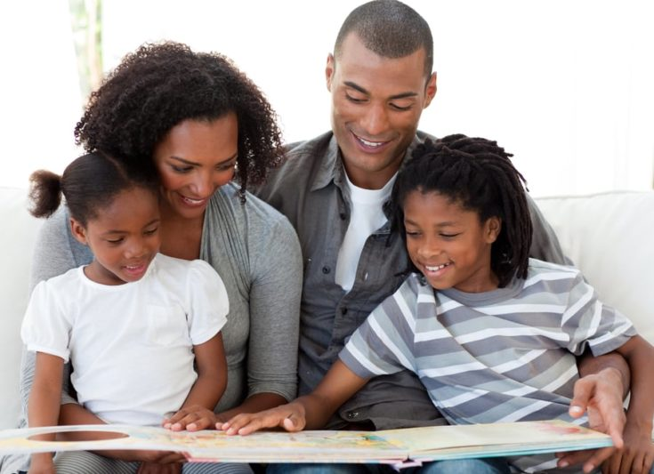 Smiling Afro-American family reading a book in the living-room