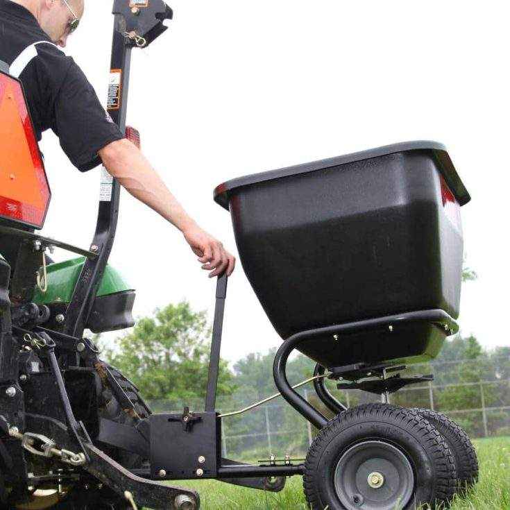 an operator using the lever that connects to a tow behind spreader