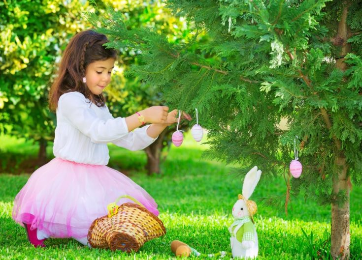 Adorable little girl having fun outdoors with Easter bunny toy, decorated fresh green tree with coloring eggs, Happy Easter holiday