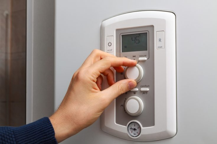 Men hand regulate temperature on 45 degree in control panel of central heating