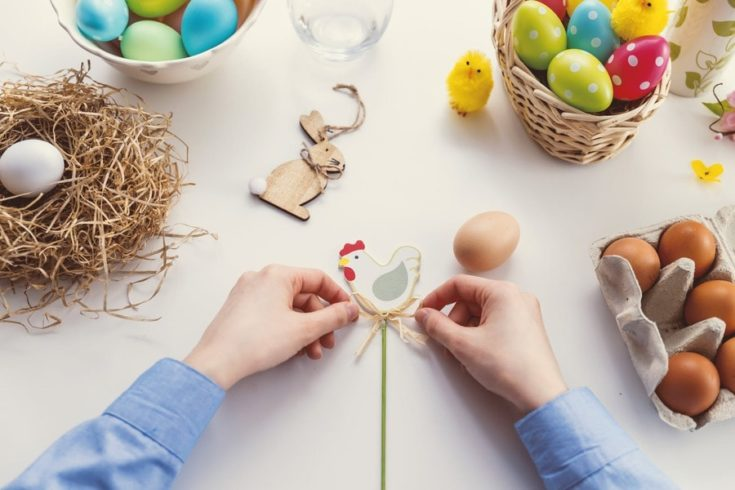 Person Tying Knot on Chicken Decor with colorful eggs on the side