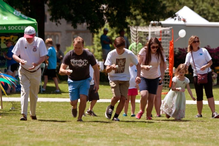 Several people run in the egg and spoon race at the GREAT festival, a spring festival celebrating Great Britain and the United Kingdom.