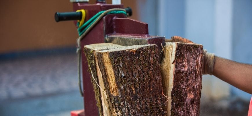 Man's hand splitting wood using log splitter