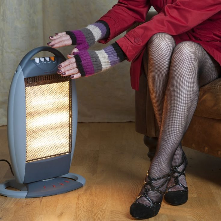 Woman using a portable electric heater