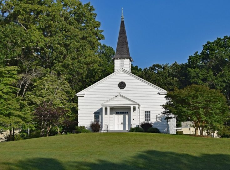 a white church in the middle of a green field with tall trees besides it
