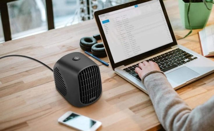 space heater on top of a working desk with a woman using her laptop