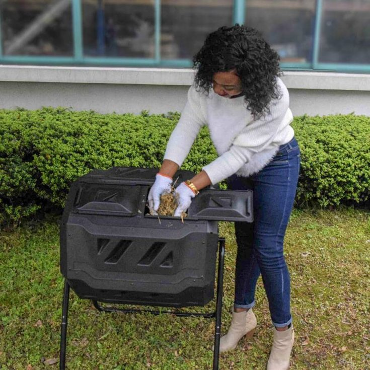 A woman loading materials into a portable composting tumbler