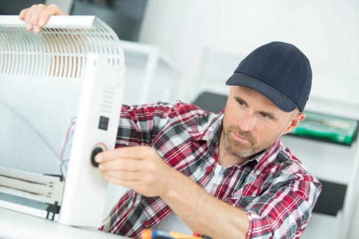 Electrician repairing heater and repair