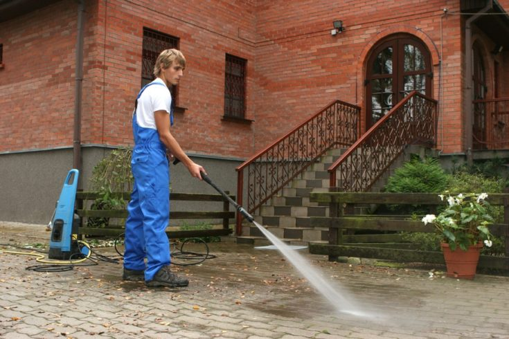 professional cleaning the walkways using pressure washer