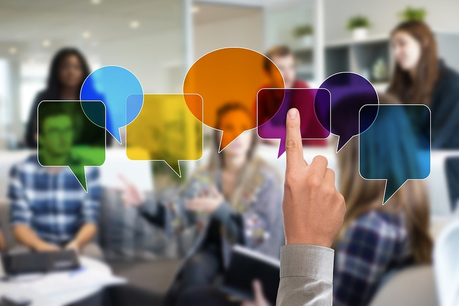 Colorful speech bubbles with a hand pointing to one of it in blurry background of people discussing