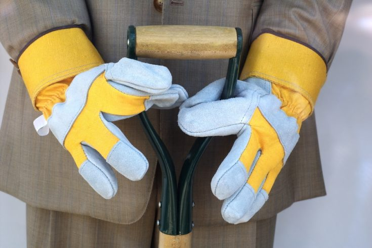 male mannequin holding shovel in business suit with garden gloves - busy life metaphor