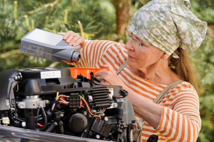 Senior woman pours oil into an outboard engine through a funnel. Breaking down the stereotypes of women - gender and age
