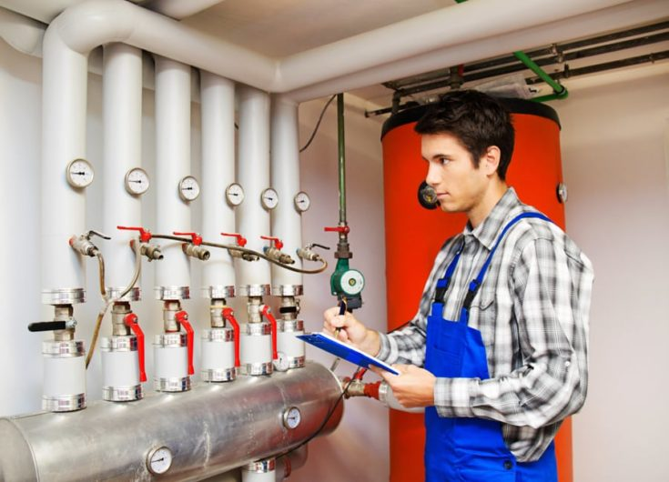 Young heating engineers in the boiler room for heating