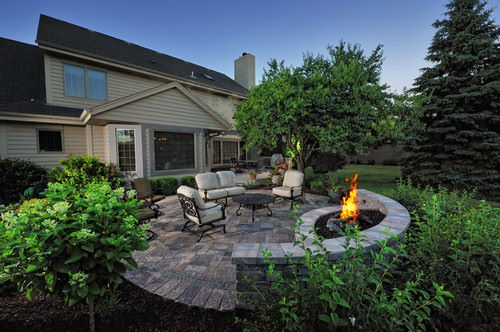 Fire pit on the backyard with table and chairs, plants
