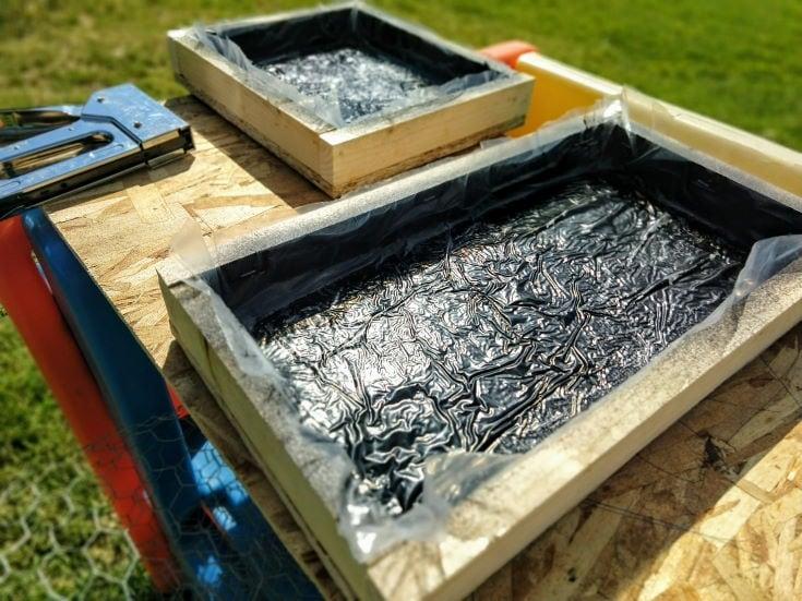 rectangular wooden box with dark cellophane on the backyard