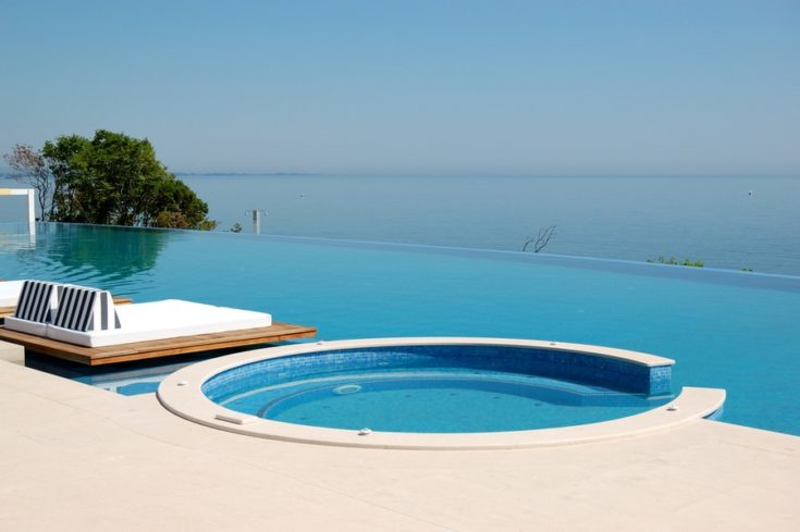 Infinity swimming pool with jacuzzi by beach