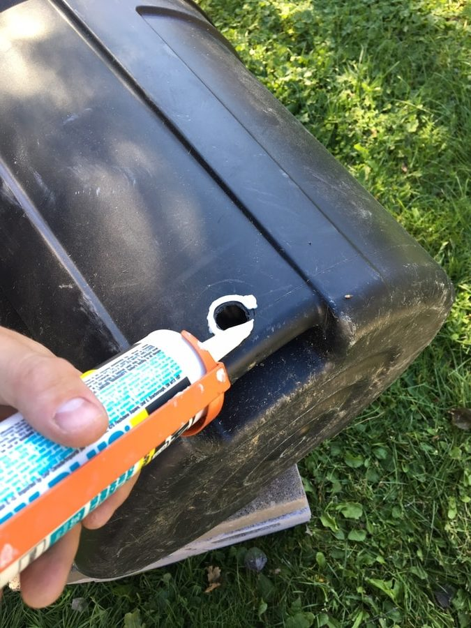 a close up shot of a hand holding a sealant to seal the hole of the plastic barrel