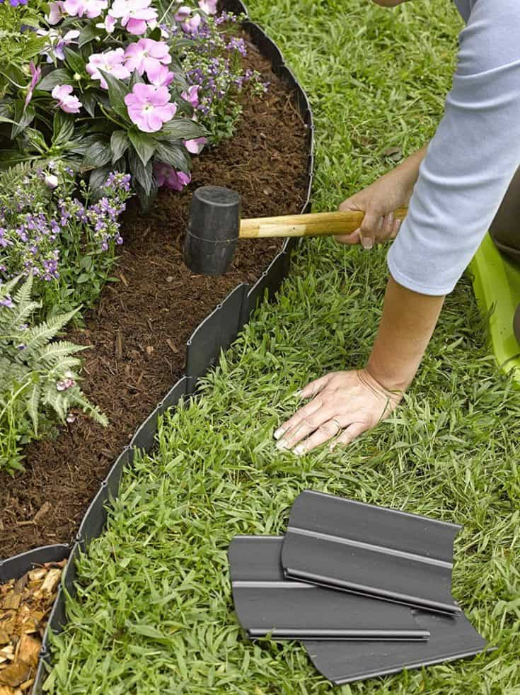 Close up woman hands holding a pallet to install metal lawn border edging.