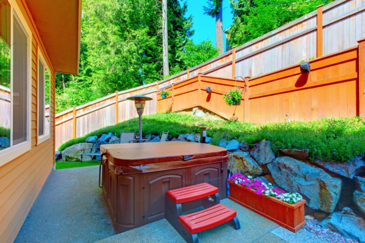 Outdoor hot tub in the back yard with natural stone landscaping and green lawn.