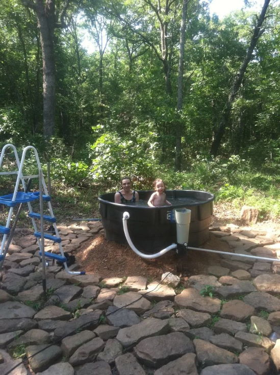 mother and baby inside a Redneck Outdoor Tub with trees at the back
