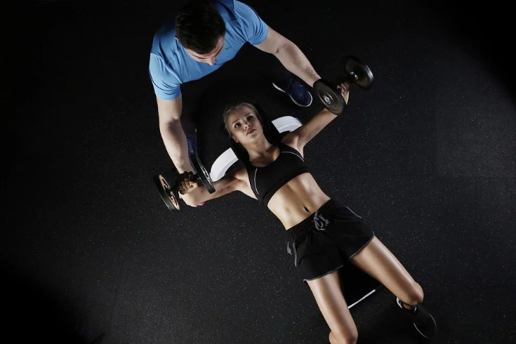 woman doing workout lying down holding both hands a dumbbell with a man assisting her