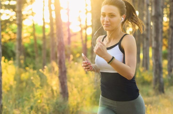 woman running wearing headset in blurry trees background