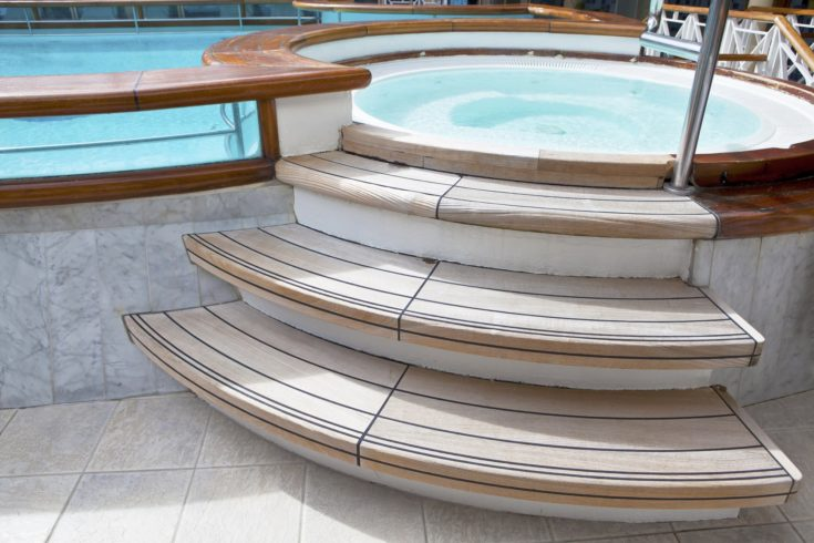 Whirlpool jacuzzi with wooden steps and pool on the deck of a cruise ship. Selective focus on steps