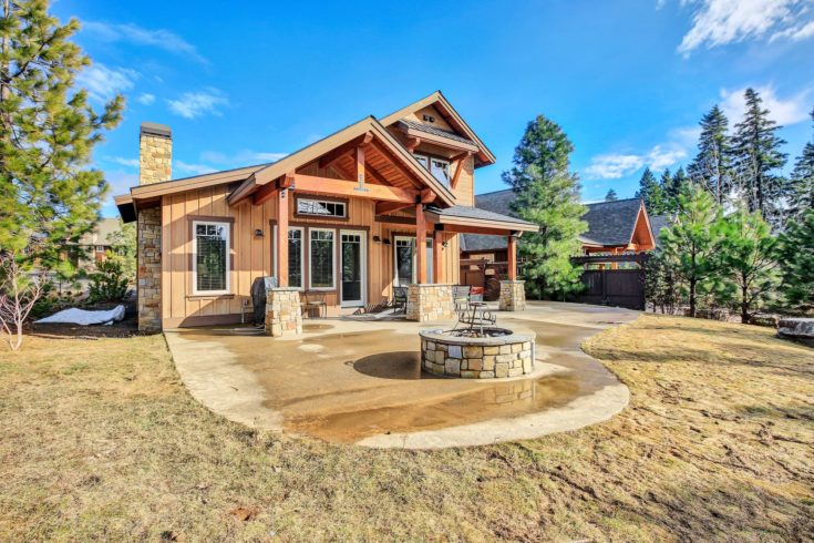 Wooden home exterior with spacious back patio, fire pit, hot tub and barbecue.