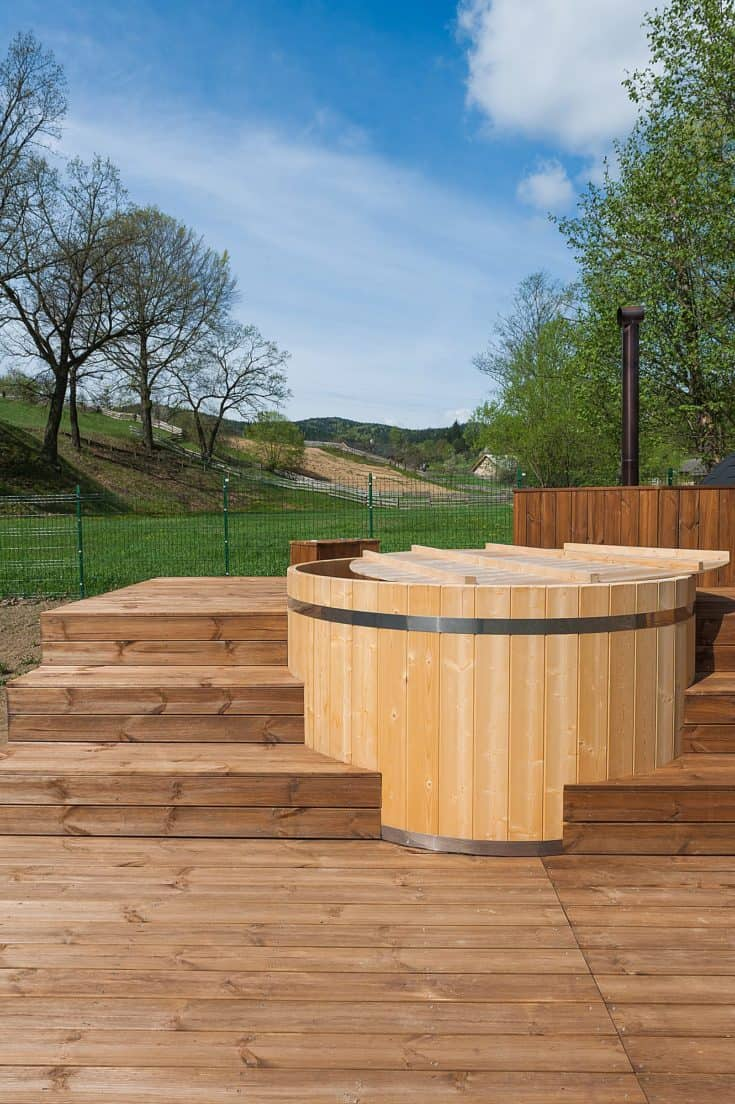 Wooden hot tub outdoor in a green field