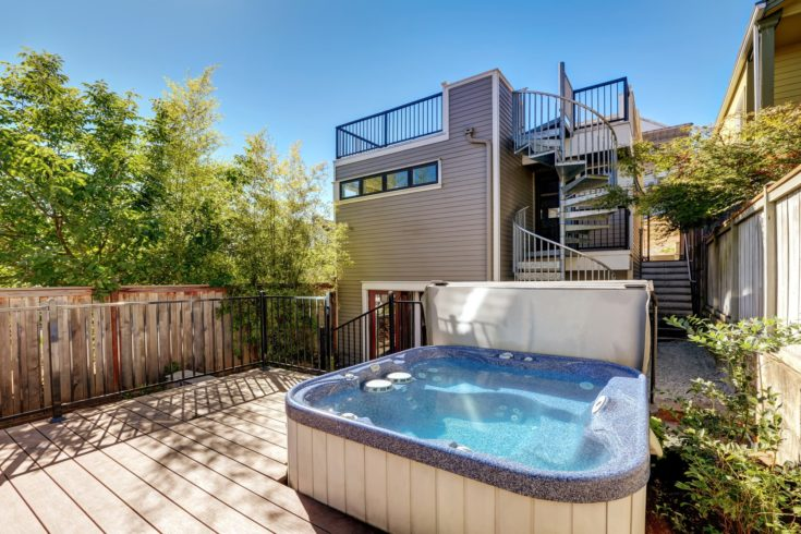 Wooden walkout deck with hot tub. House exterior in Tacoma. Northwest, USA
