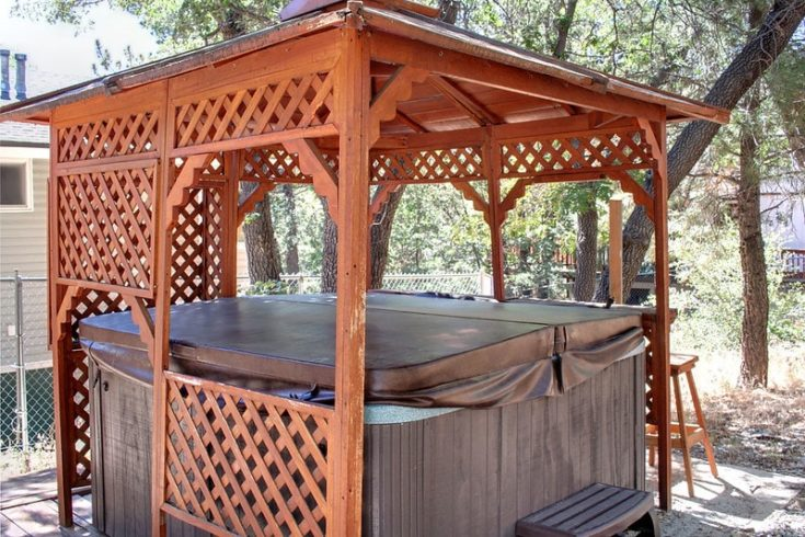 a hot tub with pergola at the backyard